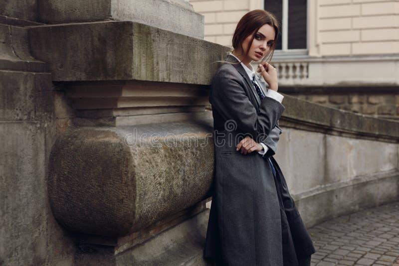 Belle femme à la mode dans des vêtements de mode posant dans la rue photographie stock libre de droits