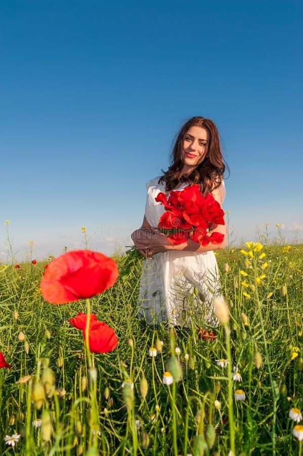 Belle femme élégante au-dessus de ciel et de coucher du soleil dans le domaine tenant un bouquet de pavots, souriant image libre de droits