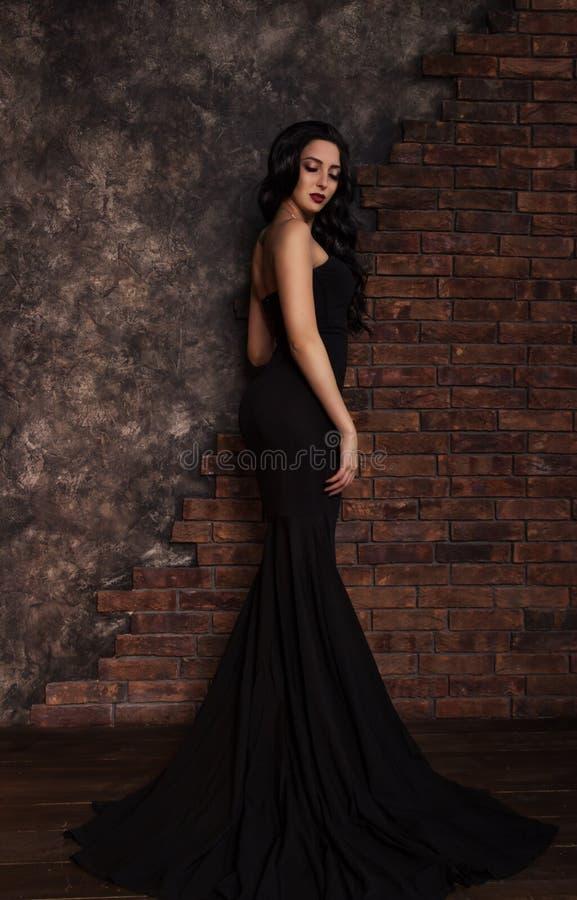 Belle femme élégante de brune dans la robe noire images stock