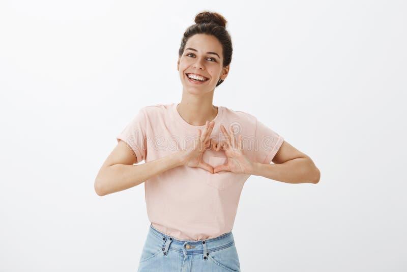 Belle femme élégante insouciante et à l'air amical dans le T-shirt rose et des jeans montrant le geste de coeur au-dessus du sour photo stock