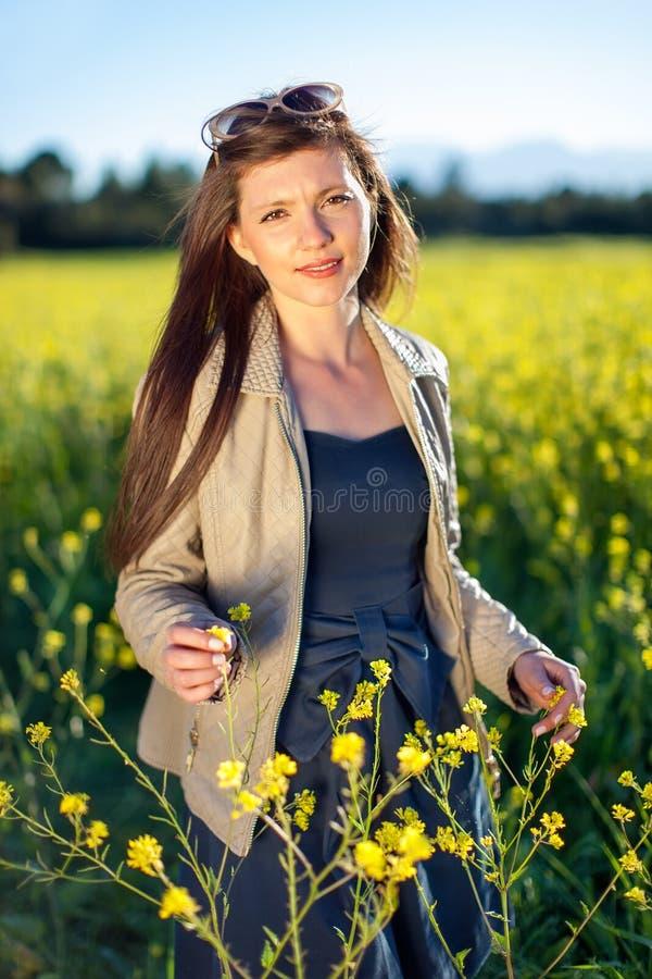 Belle femme élégante parmi les fleurs jaunes. images libres de droits