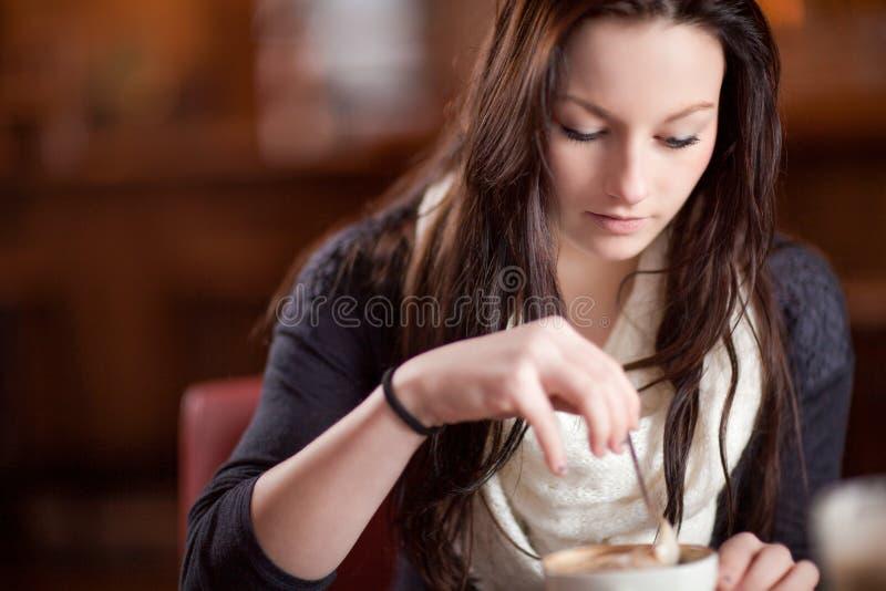 Femme remuant une tasse de cappuccino photographie stock