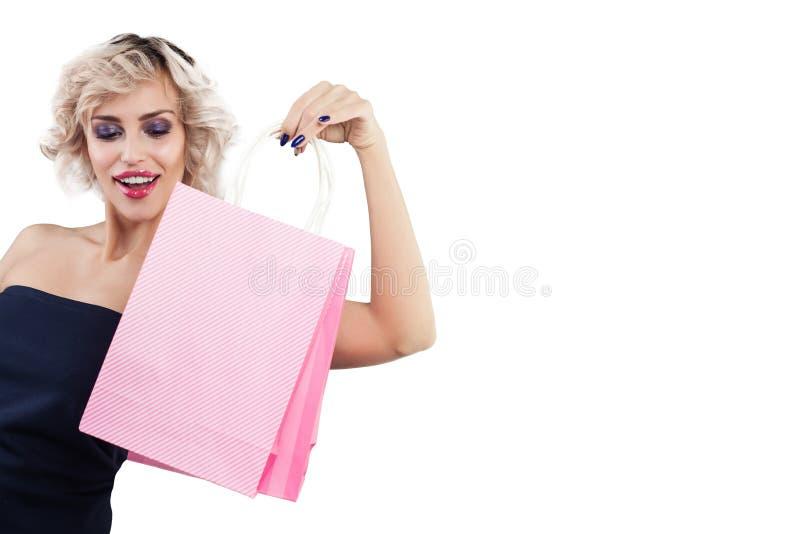 Belle femme étonnée avec le portrait de sacs à provisions sur le blanc images libres de droits