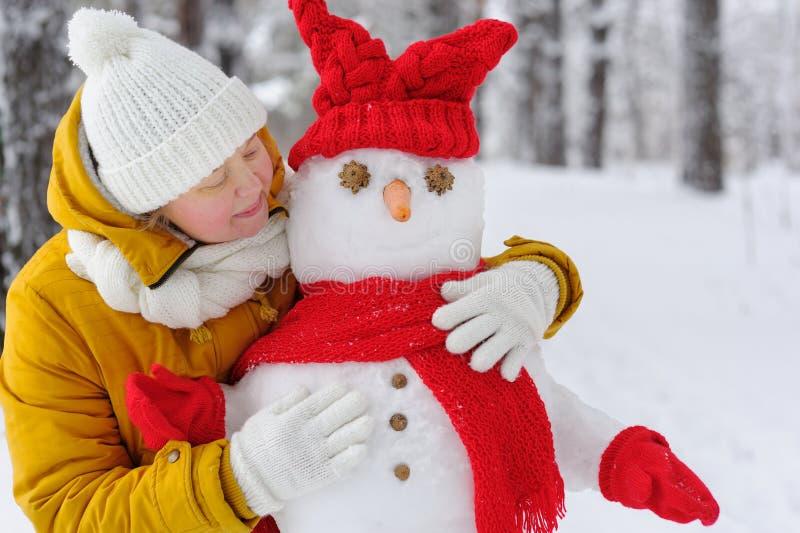 Belle femme étreignant un bonhomme de neige image libre de droits