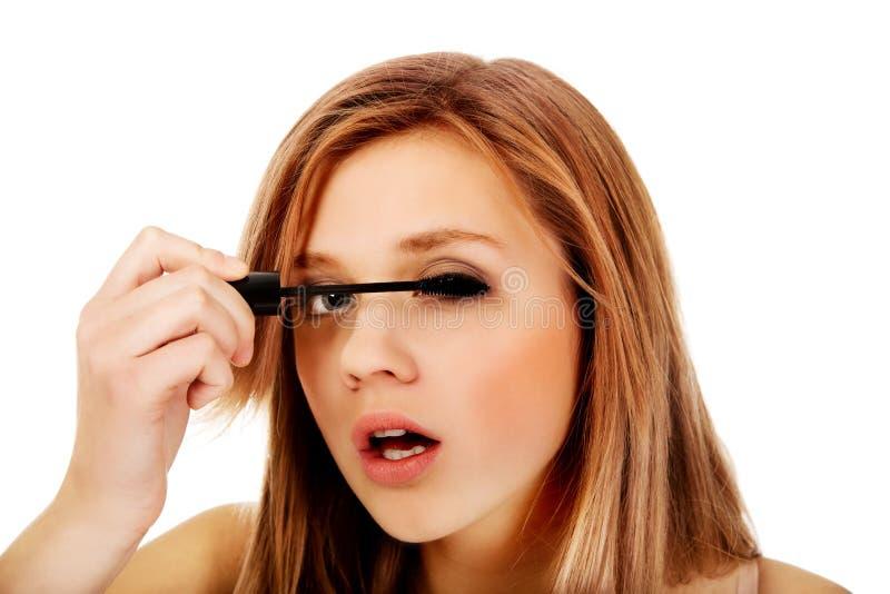 Belle femme adolescente appliquant le mascara photographie stock