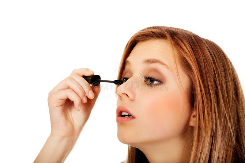 Belle femme adolescente appliquant le mascara images stock