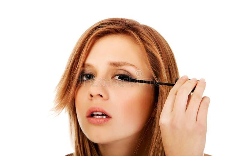 Belle femme adolescente appliquant le mascara photos stock
