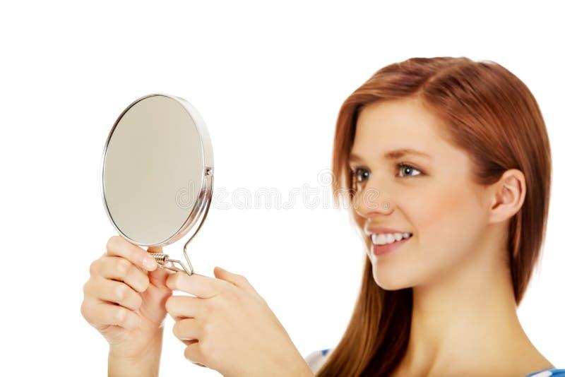 Belle femme adolescente regardant dans un miroir photo libre de droits