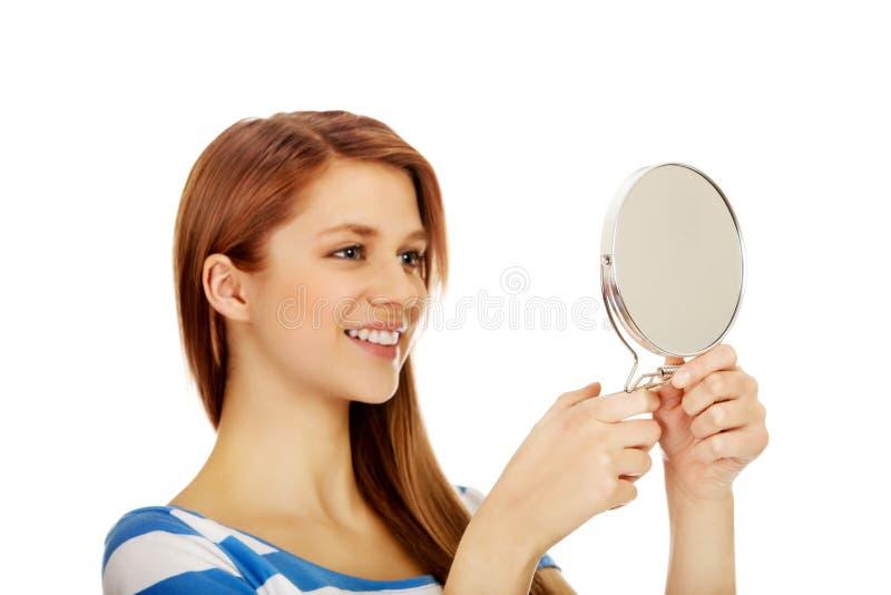 Belle femme adolescente regardant dans un miroir photo stock