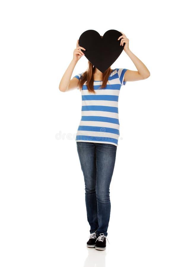 Belle femme adolescente tenant le coeur de papier photographie stock