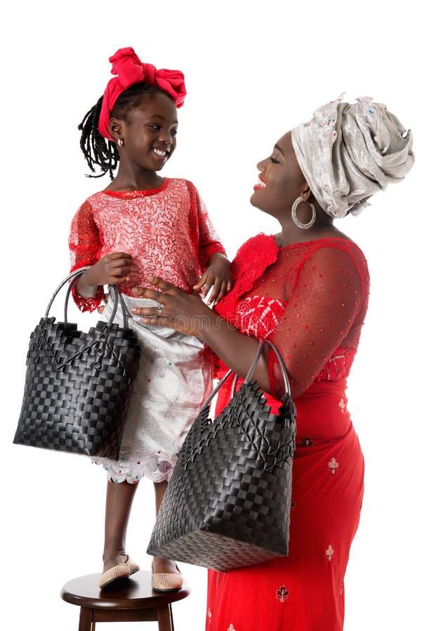 Belle femme africaine avec la petite fille dans l'habillement traditionnel photo libre de droits