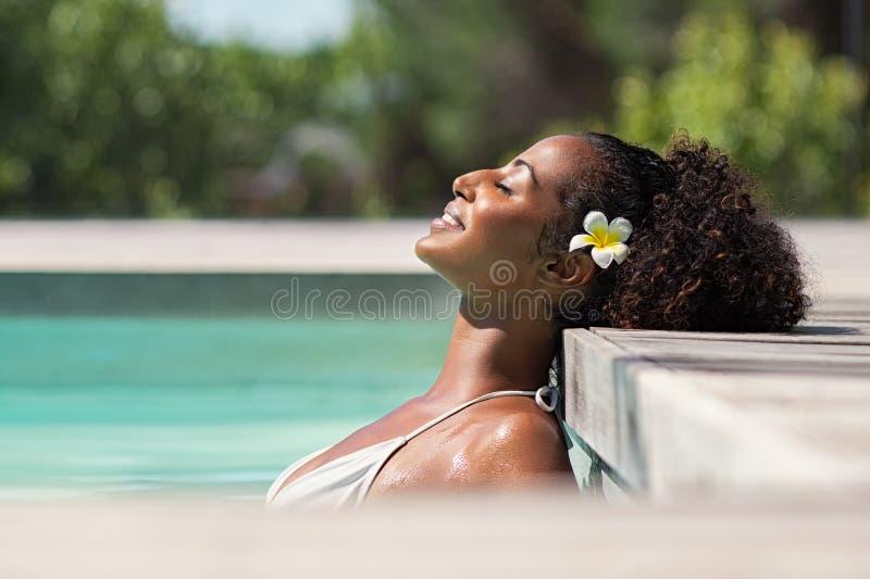 Belle femme africaine dans la détente de piscine photographie stock libre de droits