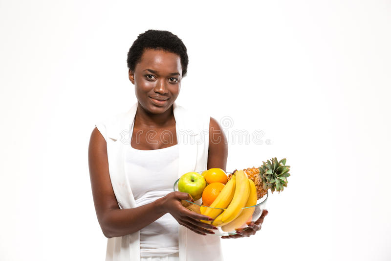 Belle femme africaine gaie tenant et tenant les fruits exotiques images stock