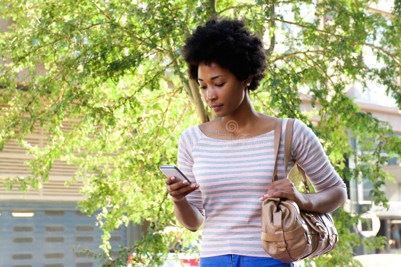 Belle femme africaine marchant dans la ville avec le téléphone portable photographie stock libre de droits
