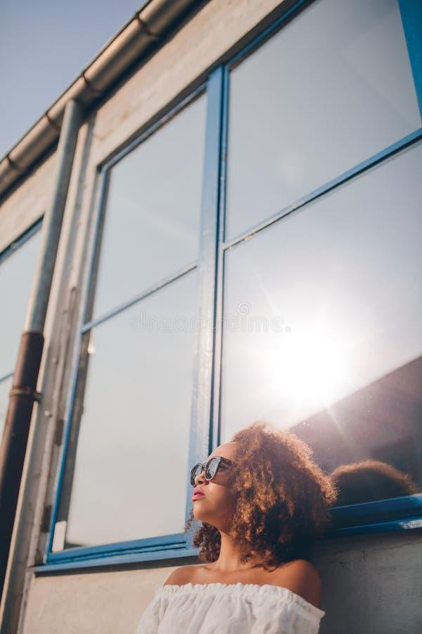 Belle femme africaine s'asseyant dehors et regardant loin photo stock