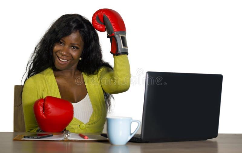 Belle femme afro-américaine noire heureuse dans le travail gai de sourire de gants de boxe au bureau d'ordinateur de bureau posan photos stock