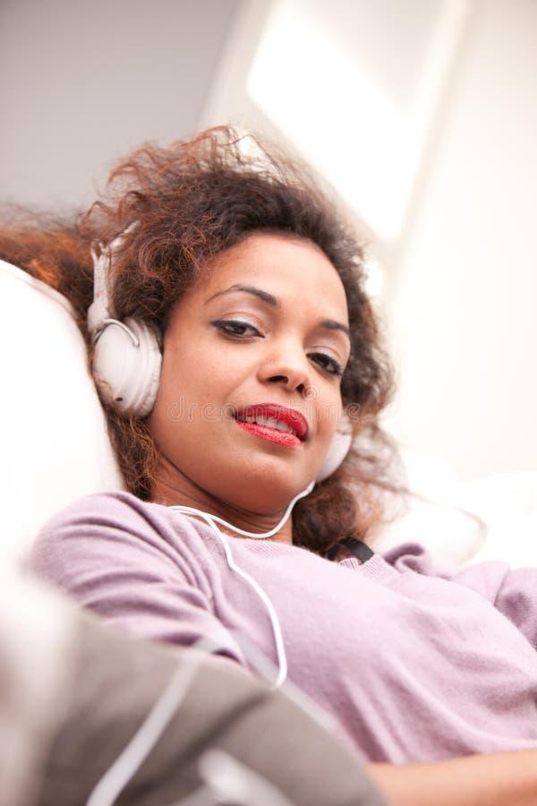 Belle femme afro-américaine sur un sofa photographie stock libre de droits