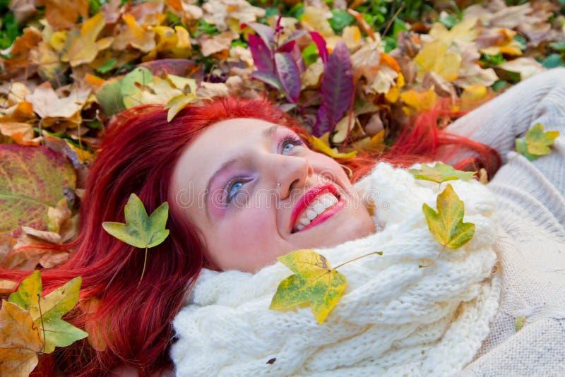 Belle femme allongée sur une feuille d'automne rouge photos libres de droits