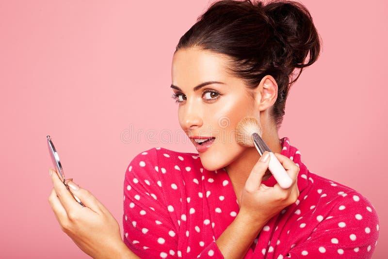 Belle femme appliquant le blusher photo stock