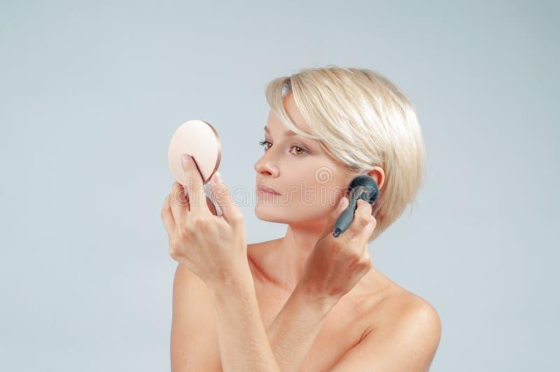 Belle femme appliquant le maquillage avec la brosse de poudre sur le visage regardant un miroir photographie stock