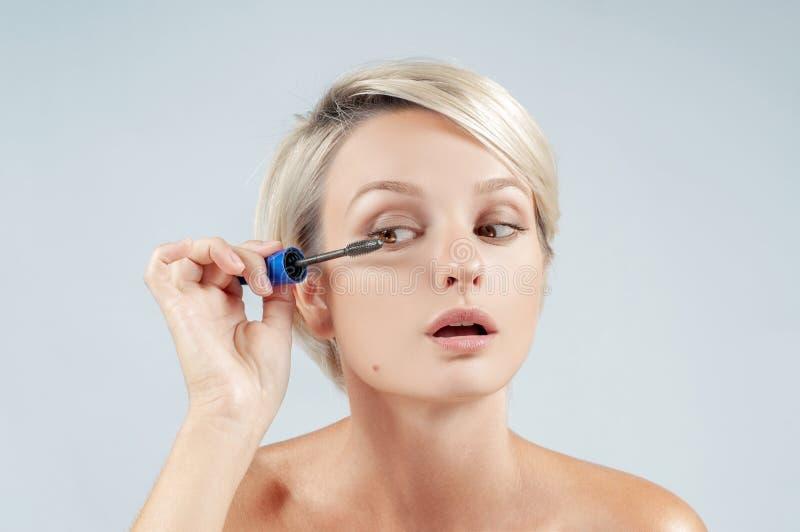 Belle femme appliquant le maquillage de mascara sur des yeux par la brosse images libres de droits