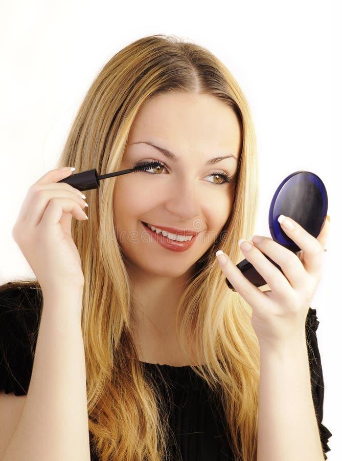 Belle femme appliquant le mascara image stock