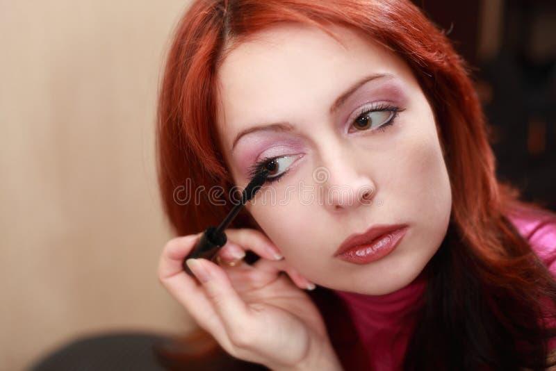 Belle femme appliquant le mascara sur des cils images stock