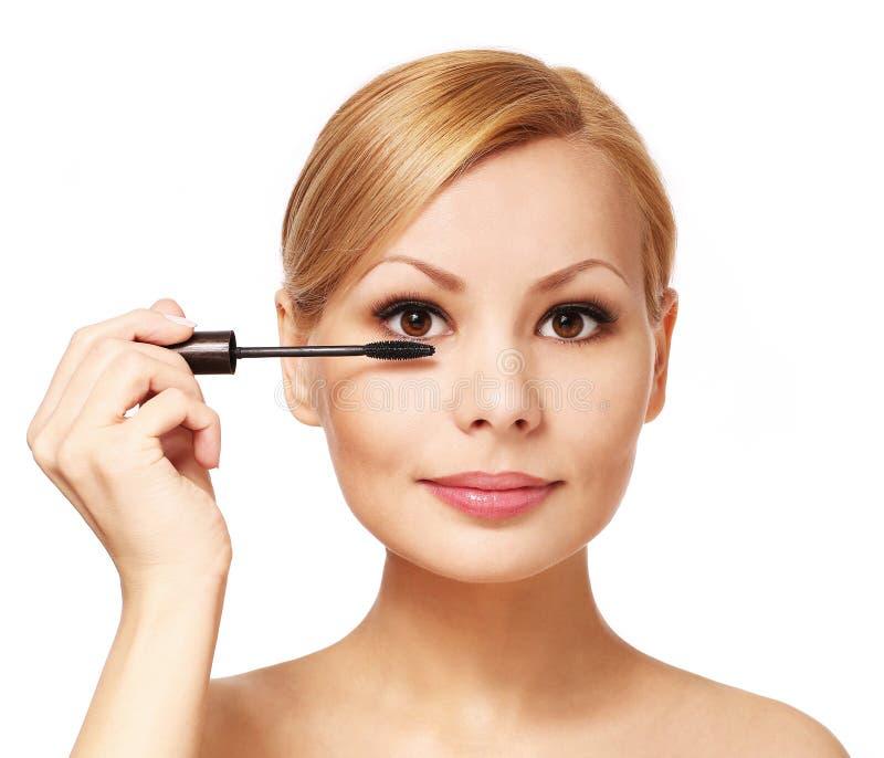 Belle femme appliquant le mascara sur ses cils, d'isolement images stock
