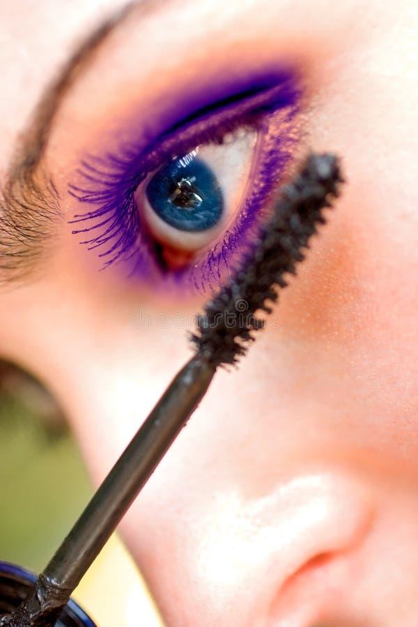 Belle femme appliquant le mascara sur son oeil image libre de droits