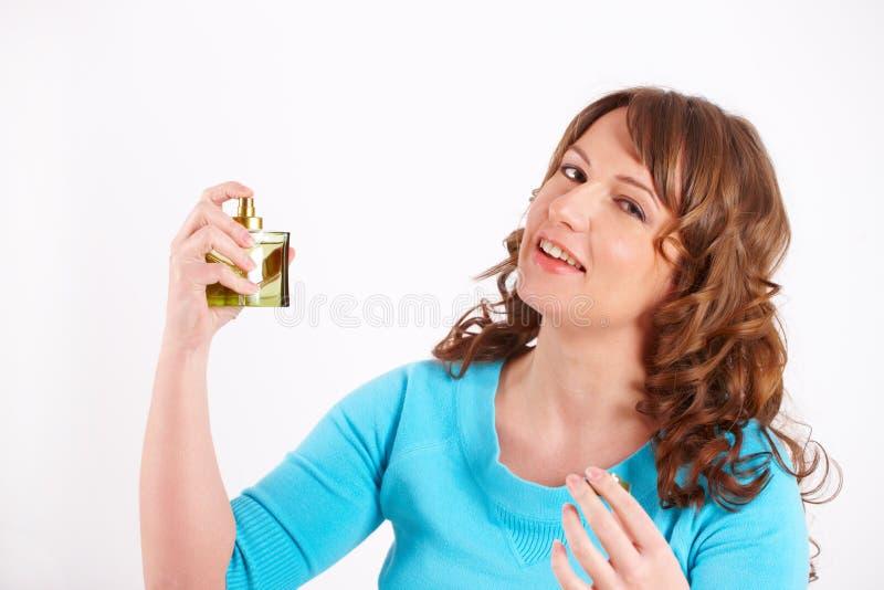 Belle femme appliquant le parfum images stock
