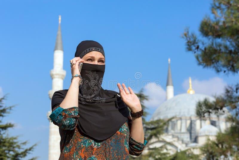 Belle femme Arabe dans l'habillement musulman traditionnel parlant au téléphone photo libre de droits