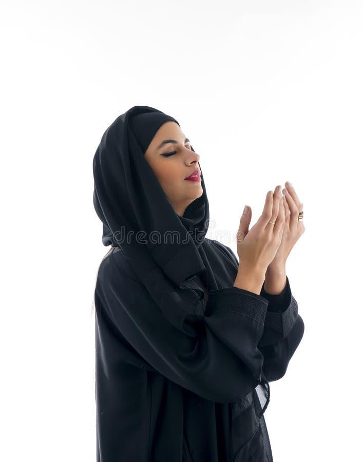 Belle femme arabe musulmane priant sur le gris photo stock