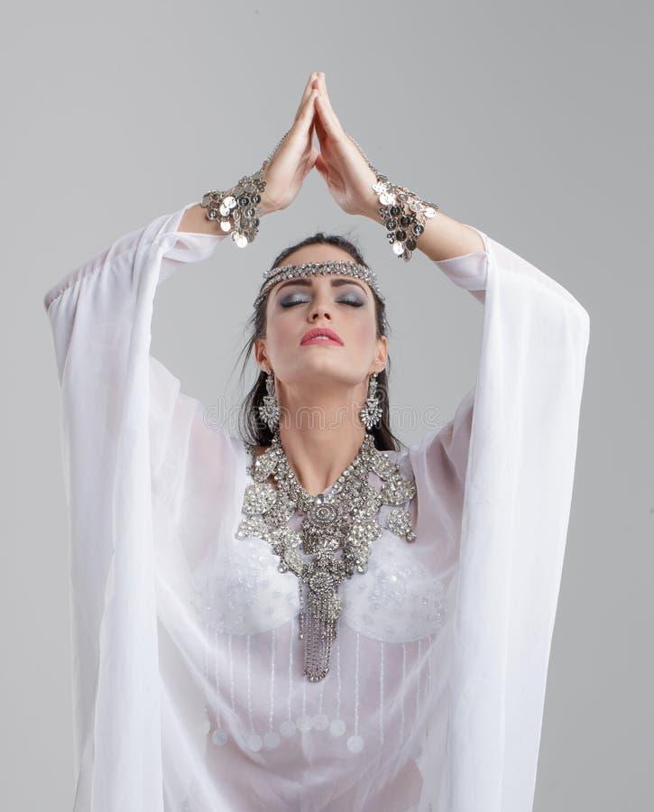 Belle femme arabe priant sur le gris images libres de droits