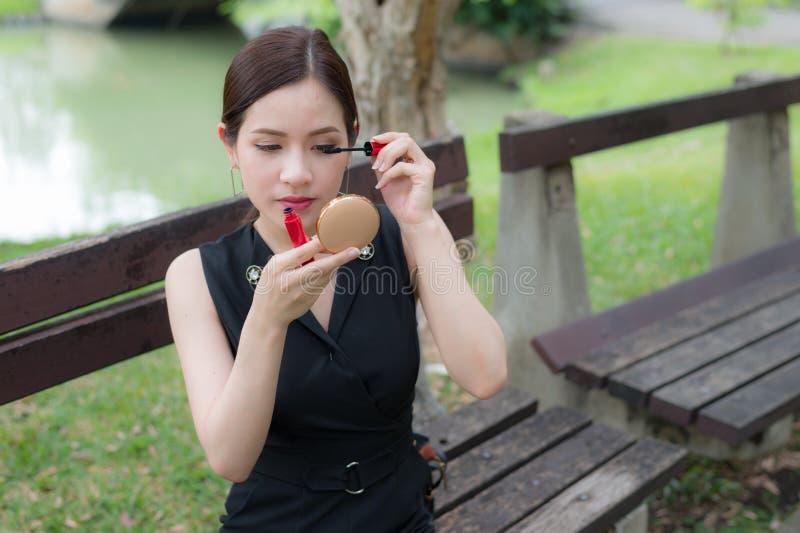 Belle femme asiatique appliquant le mascara noir sur des cils avec la brosse de maquillage images libres de droits