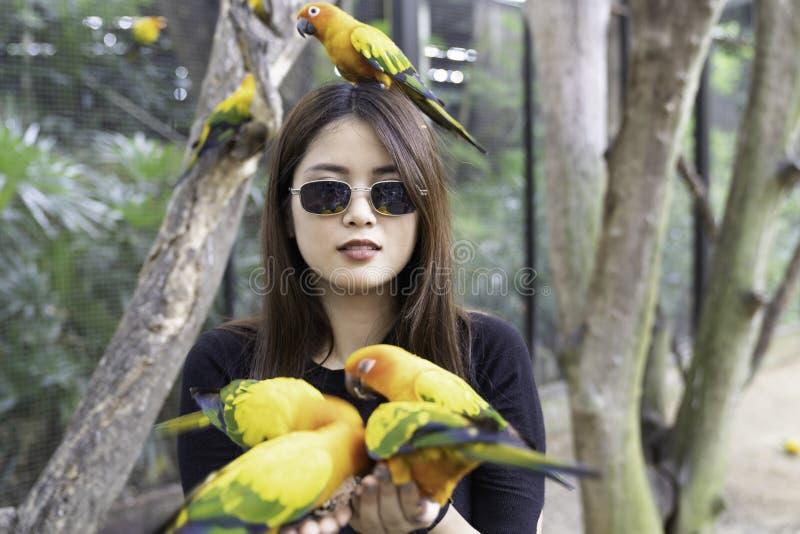 Belle femme asiatique appr?ciant avec l'oiseau d'amour en main et le corps photographie stock libre de droits