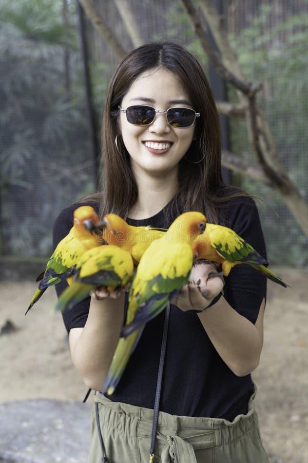 Belle femme asiatique appr?ciant avec l'oiseau d'amour en main et le corps photos libres de droits