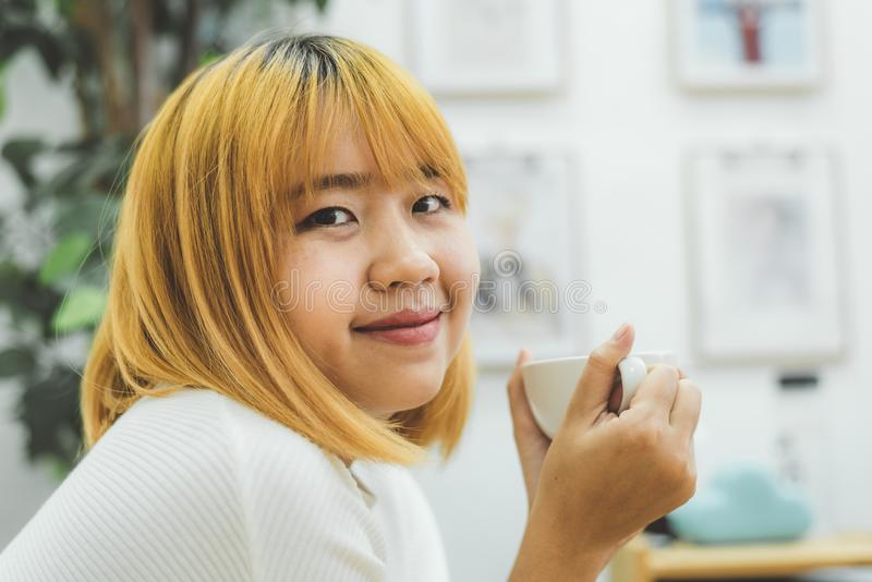 Belle femme asiatique attirante appréciant le café chaud dans la cuisine à sa maison photos stock