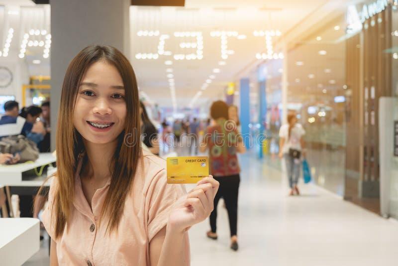 Belle femme asiatique avec carte de crédit fond flou, shopping et mode de vie photos libres de droits