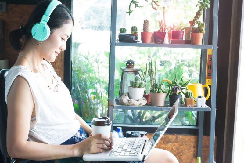 Belle femme asiatique avec des écouteurs observant le film par ordinateur portable Mode de vie et technologie photo stock