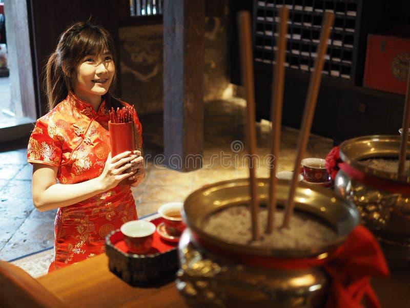 Belle femme asiatique avec l'habillement de tradition tenant le cylindre en bambou des bâtons de Chi de Chi ou du Chien Tung, Cou photo libre de droits