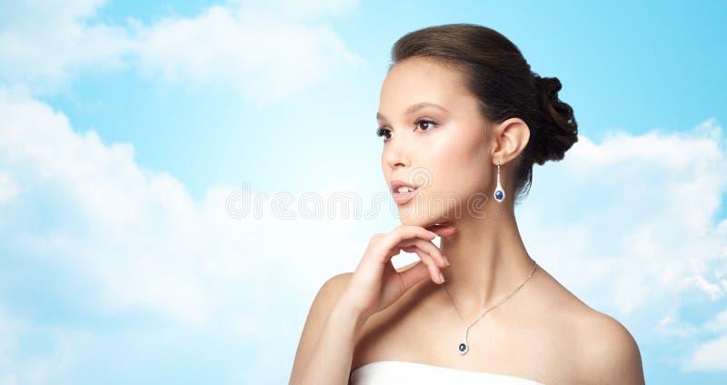 Belle femme asiatique avec la boucle d'oreille et le pendant photos stock