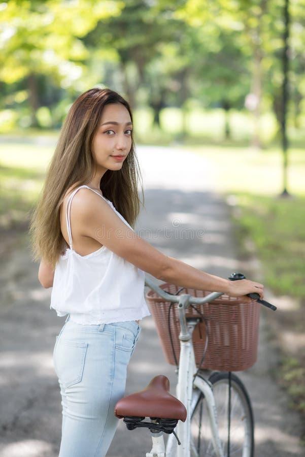 Belle femme asiatique avec le vélo en parc photo stock