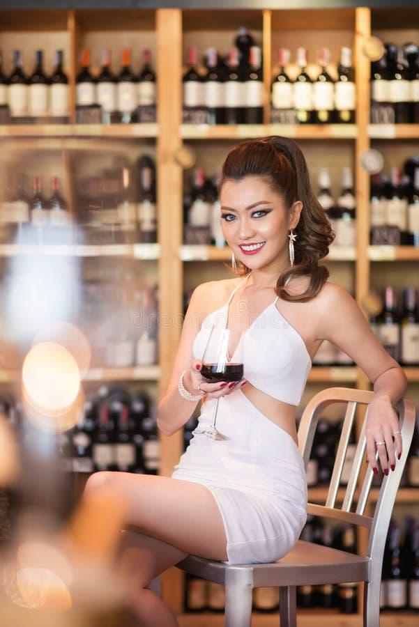 Belle femme asiatique avec un verre de vin image stock