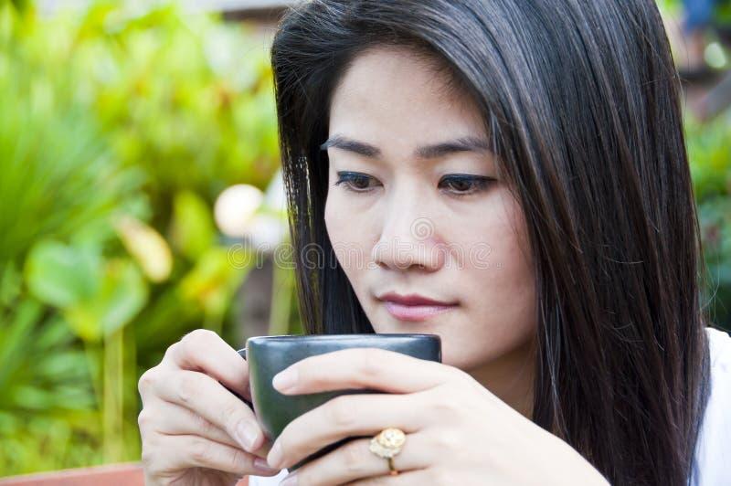 Belle femme asiatique avec une cuvette de café. photos stock