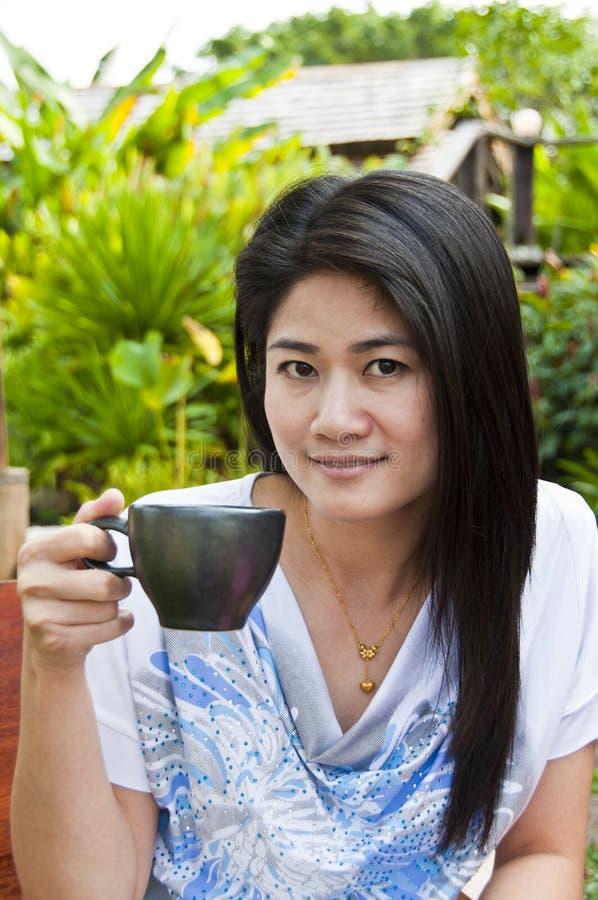 Belle femme asiatique avec une cuvette de café. image libre de droits