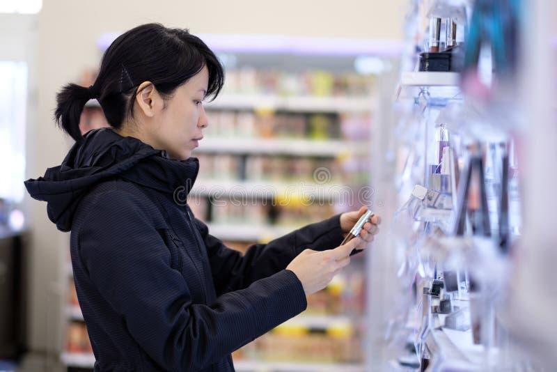 Belle femme asiatique choisissant le produit de soin personnel dans le supermarché image stock