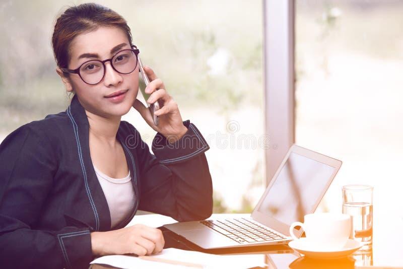 Belle femme asiatique d'affaires tenant le téléphone et appeler futés, image stock