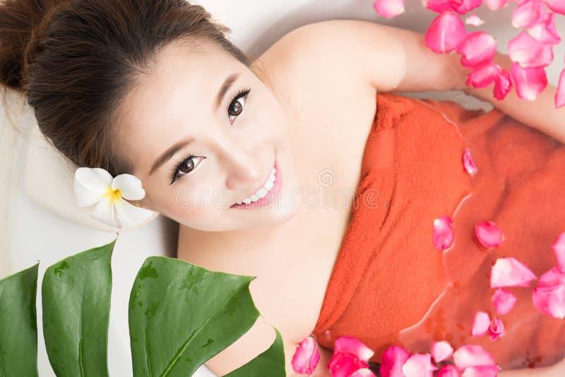 Belle femme asiatique de beauté dans le bain avec le pétale de rose Soin et station thermale de corps photos stock