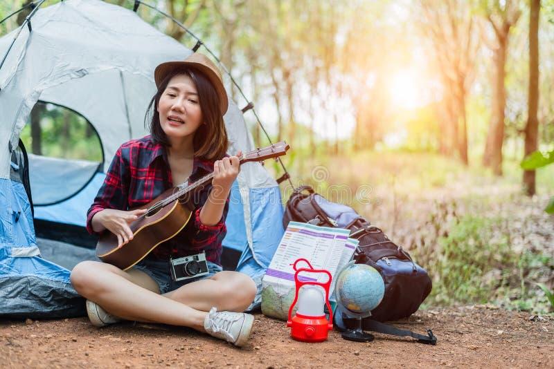 Belle femme asiatique jouant l'ukulélé devant la tente de camping en bois de pin Les gens et le concept de modes de vie Aventure  photographie stock libre de droits