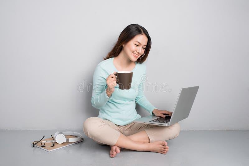 Belle femme asiatique occasionnelle heureuse travaillant sur un ordinateur portable reposant o image stock